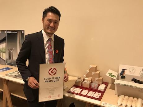グッドデザイン賞の賞状を手に岡正純さん