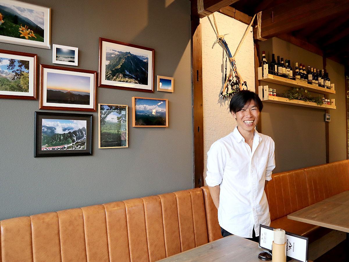 登山写真の前に立つ斎藤さん