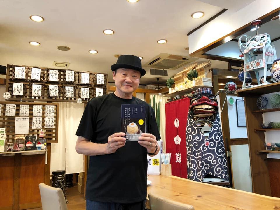 慈げん店内で書籍を手にする店主の宇田川和孝さん