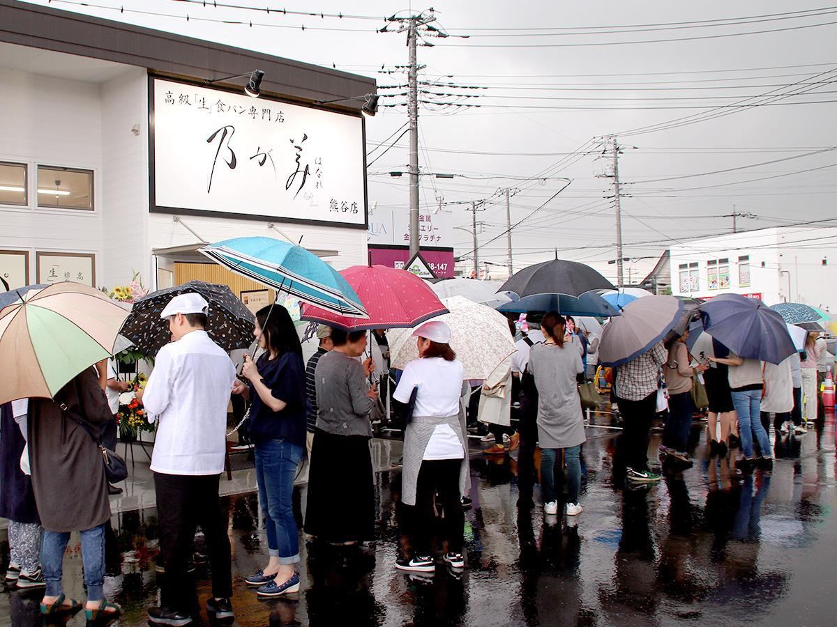 雨の中、傘をさして並ぶ来店客の列