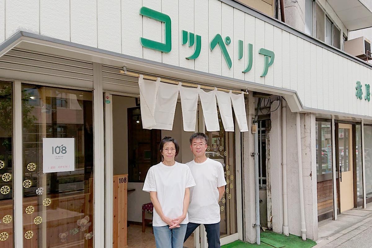 旧店名「コッペリア」と書かれた店前に立つ八木さん夫妻