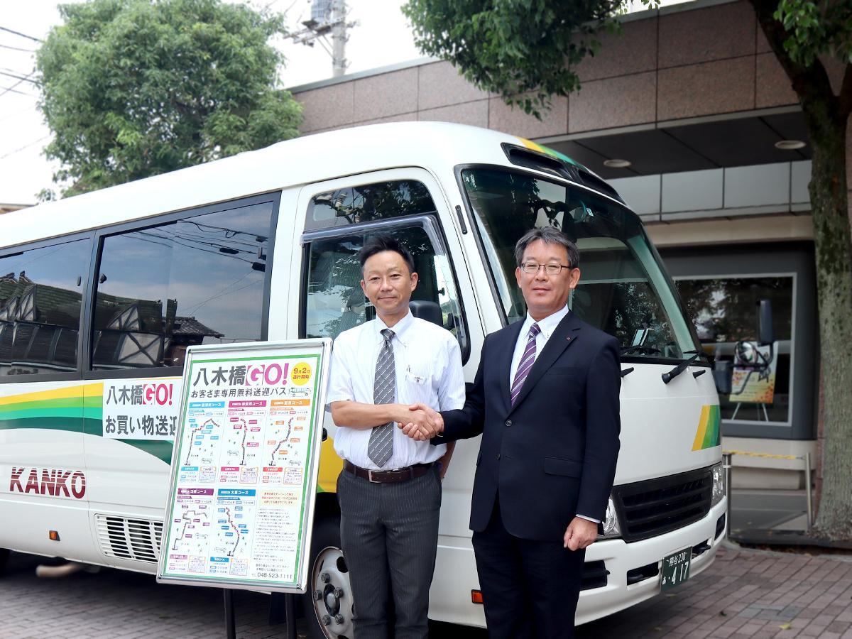 無料送迎バスの前で握手を交わす八木橋百貨店担当者と協同バスの鈴木社長