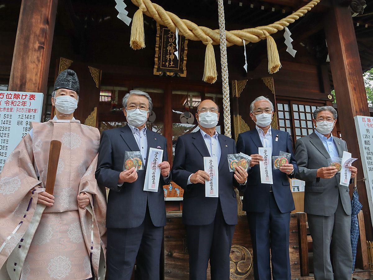 新型コロナウイルス感染症を封じる「疫病退散特別祈祷」が行われた行田八幡神社で「疫病封じの札」を手にする関係者ら