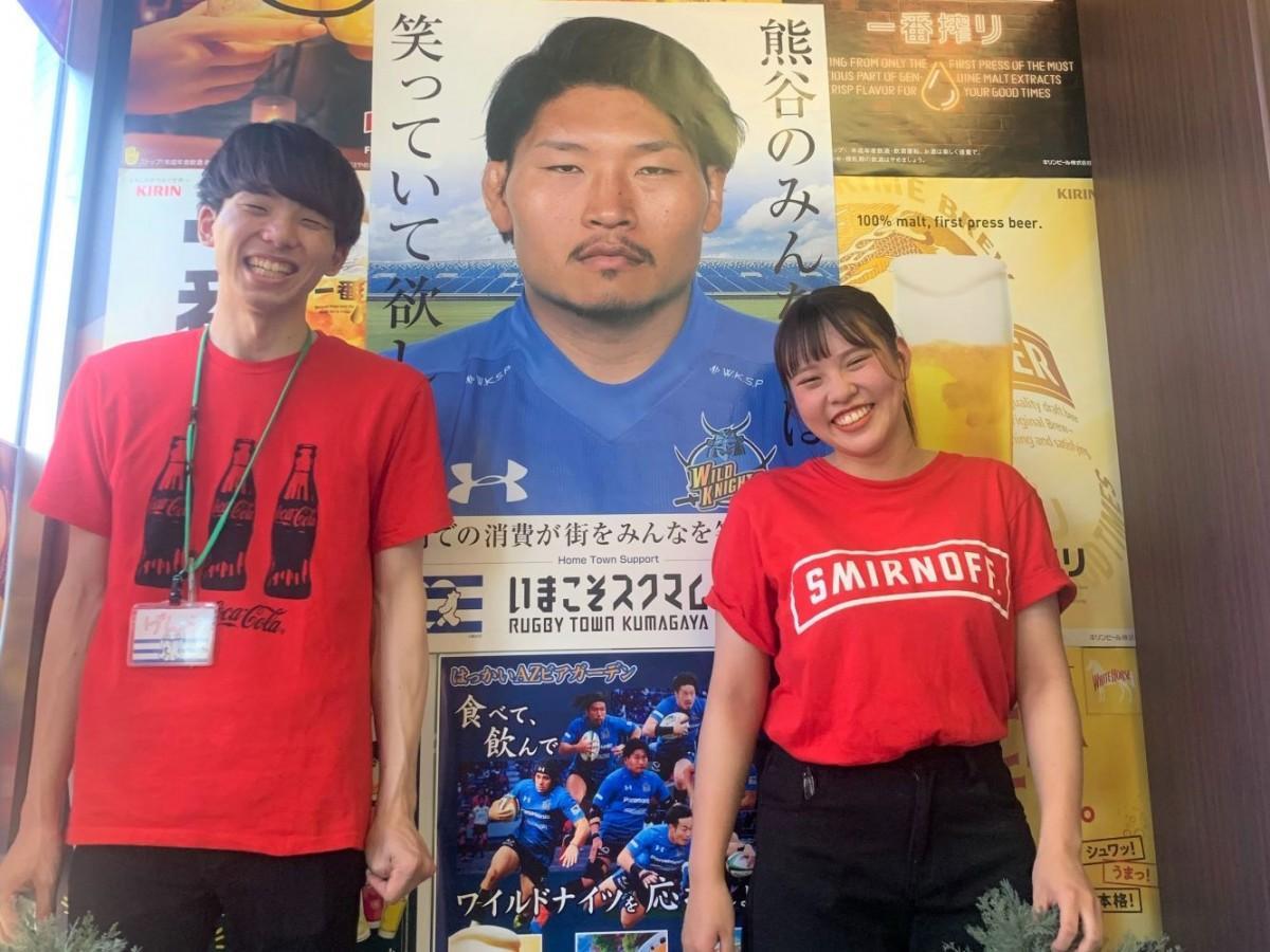パナソニックワイルドナイツとコラボした同店オリジナルポスターと「笑わない男」稲垣選手のポスターの前で来店を呼び掛けるスタッフ