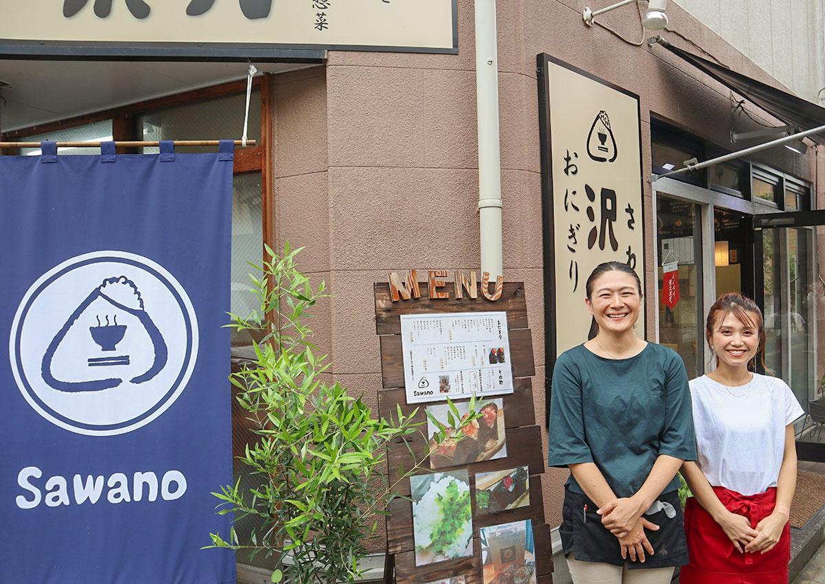 おにぎりのロゴが大きく描かれたのれんと看板が目印。店前に建つ清宮さんとスタッフ
