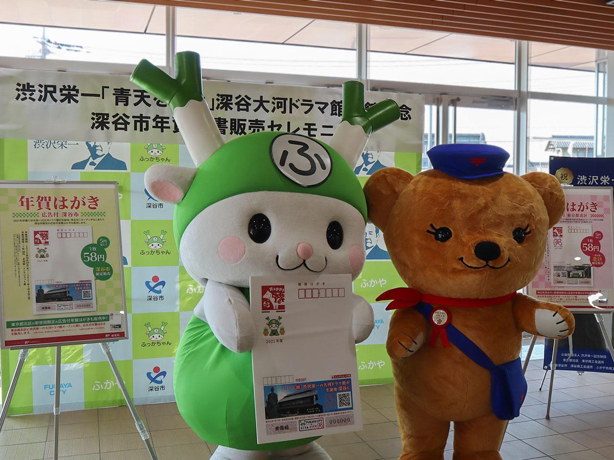 渋沢栄一年賀はがき(パネル)を手に記念撮影に応じる「ふっかちゃん」と日本郵便のキャラクター「ぽすくま」
