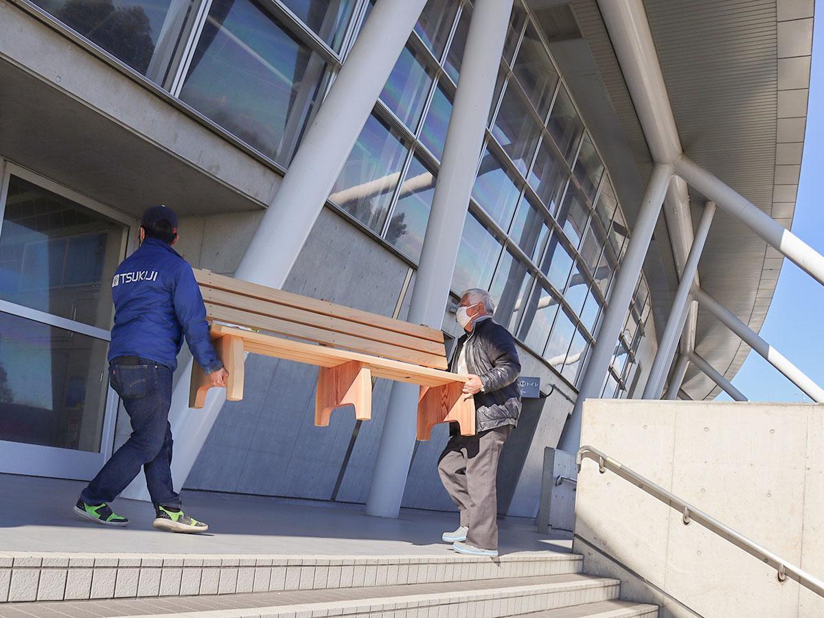 彩の国くまがやドームに木製ベンチを運び込む築地社長とスタッフ