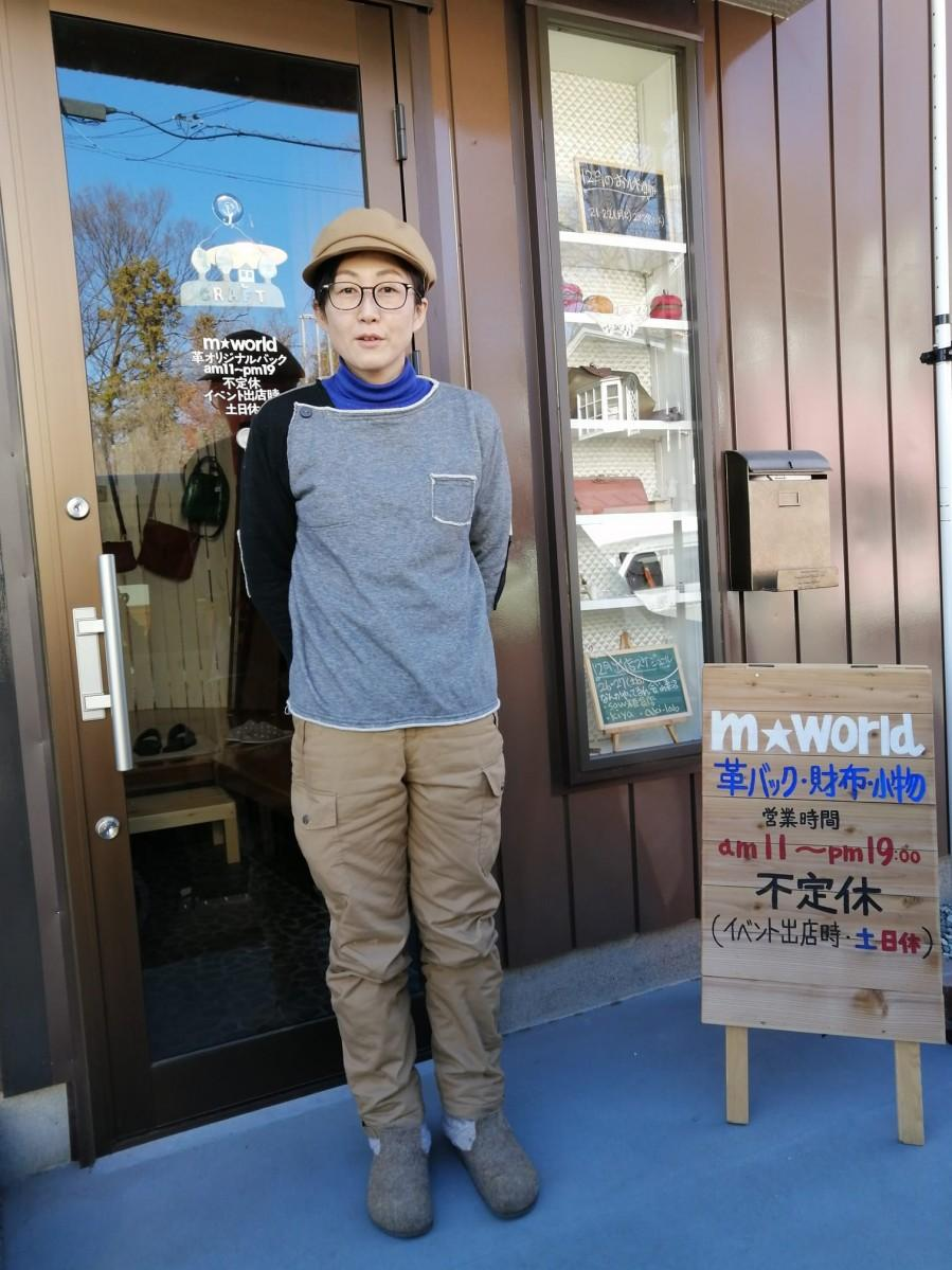 縁結び通りにある店舗前に立つ長谷川さん