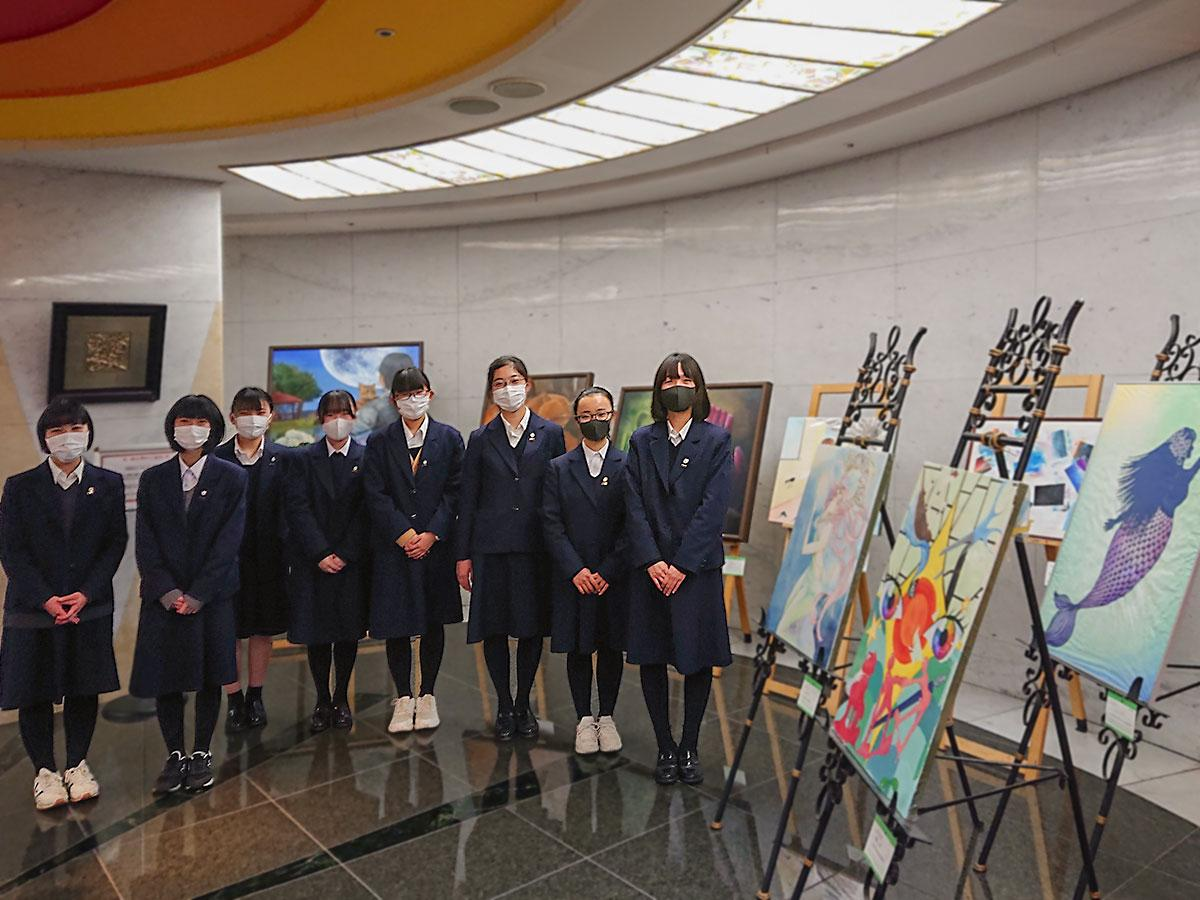 ホテル2階のロビー空間に展示した作品前に集まった美術部の皆さん