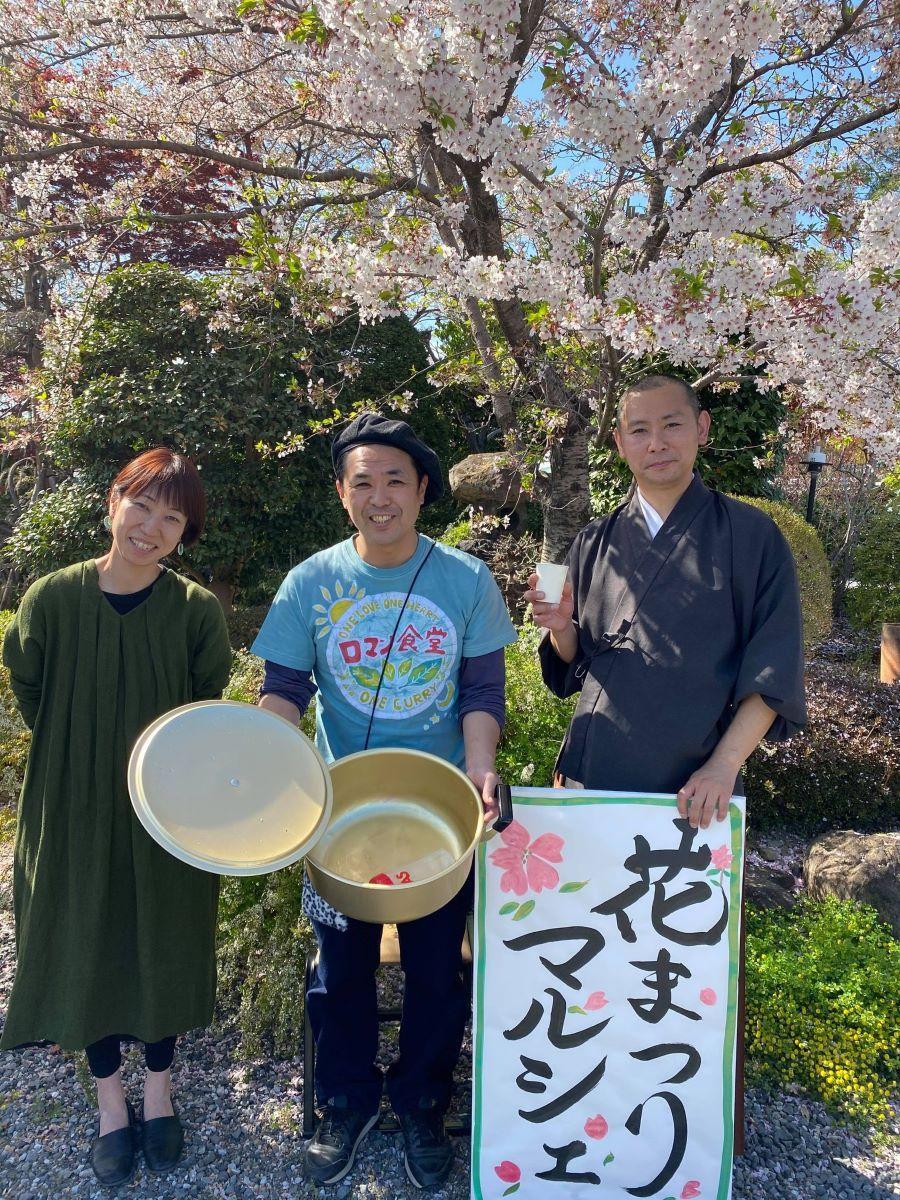 「お寺がみなさんの交流の場になってほしい」と話す住職の光栄澄人さん(右)と妻のみほ子さん(左)、完売したカレー鍋を持つ岡野さん(中央)