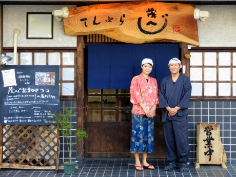 「てんぷら 茂へじ」の守屋茂さんと田中京子さん。看板の文字は守屋さんの手彫り