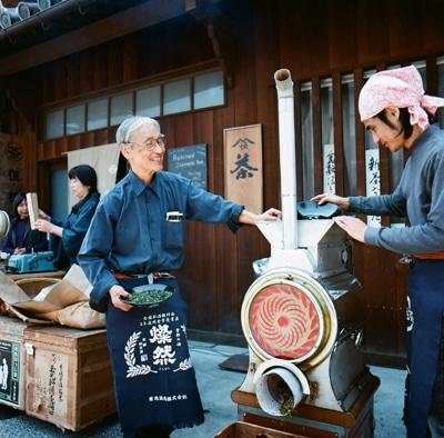 店先でほうじ茶を焙煎する恒枝信雄さんと三男の信三さん