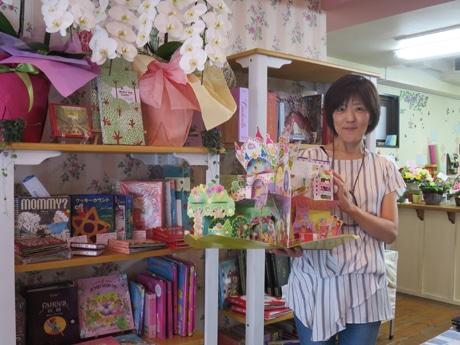 360度広がる仕掛け絵本を持つ店主の森睦子さん