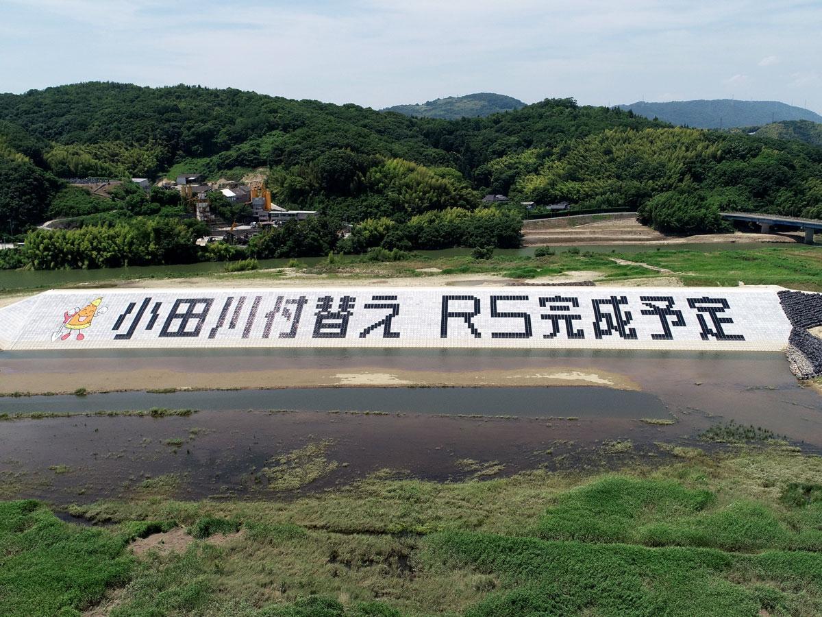 護岸にペイントされた「ファイト!」「小田川付替えR5完成予定」の文字