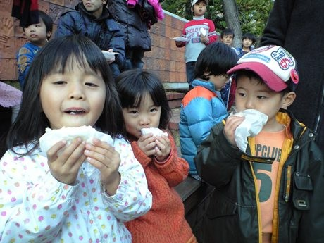 マンションで自分たちで作ったお米をほおばる子どもたち