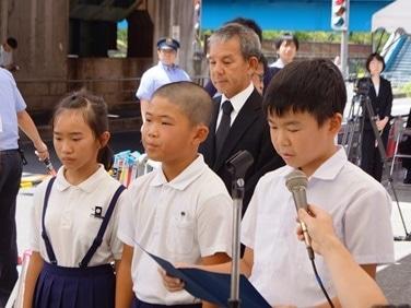 慰霊祭で作文を読む聖賢小学校6年生。左から釜谷愛莉さん・森口宏祐さん・津守陸さん。後ろは甲斐清二校長