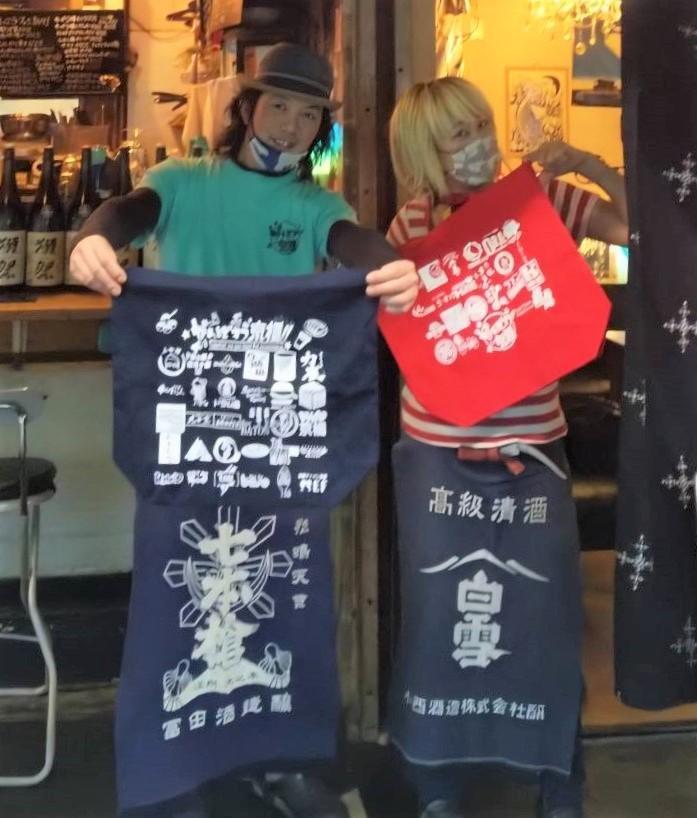 「がんばれ京橋」のチャリティーエコトートバッグを手に持つ「酒場しろくま」の増田光平さん、未歩子さん