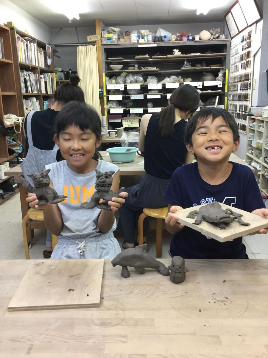 夏休みの陶芸体験でシーサーを作る小学生たち