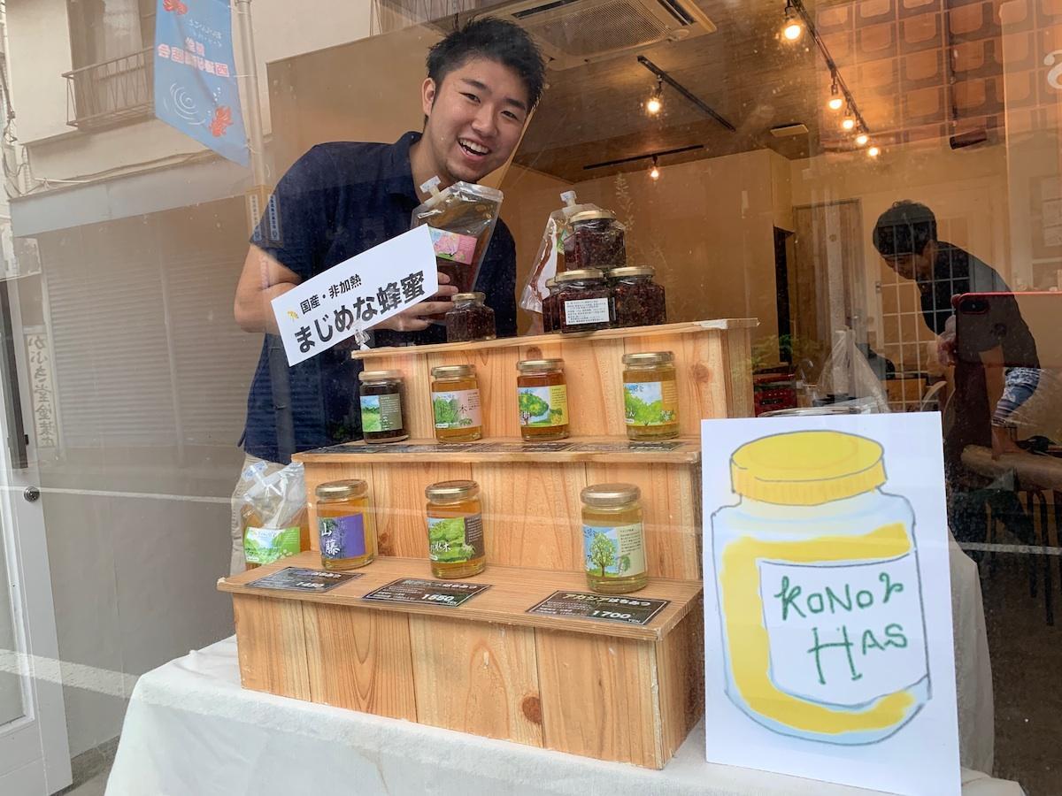 経堂西通りに面する「OReNAS(オリナス)」コワーキングスペースの窓辺。蜂蜜を持つのは社長の小澤さん