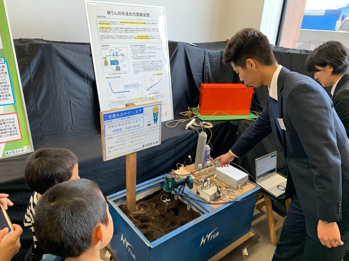 「バイオロボティクス研究室 田島ゼミ」の展示。土を掘り返し環境を破壊することなく土壌の状態を確認できる「局所耕うん同時通気性試験装置」の説明を子どもたちにする農大生