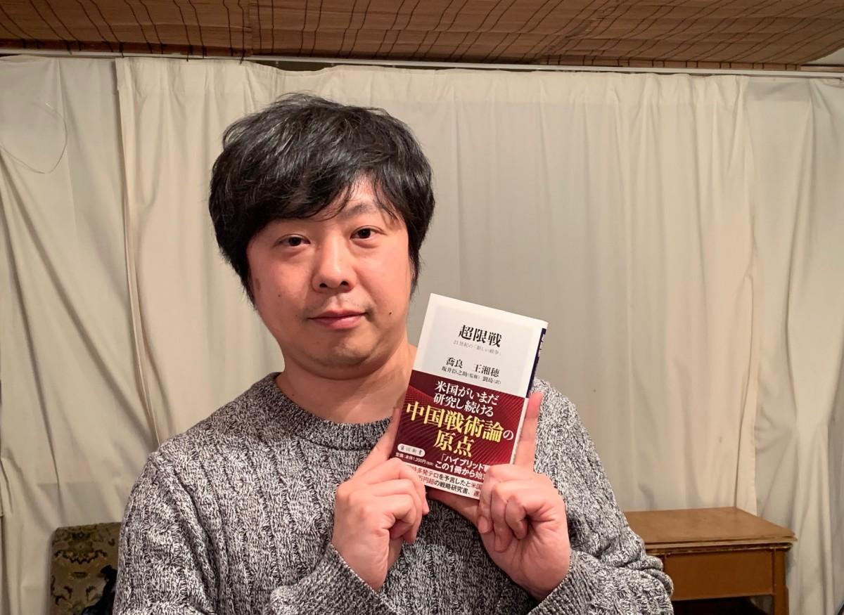 1月に出版した「超限戦」を手にする菊地悟さん