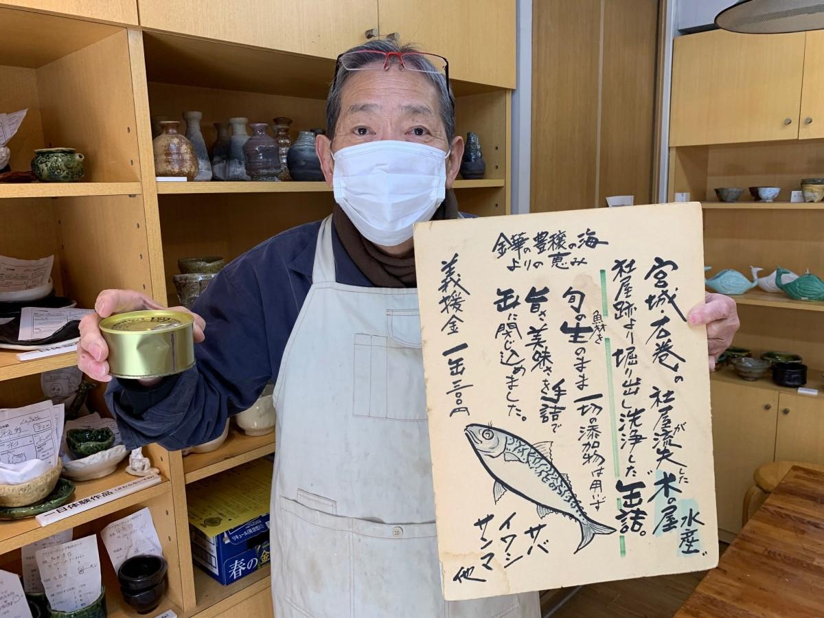 2011年4月に描いた販売用のボードと洗った缶詰を持つマスク姿の李さん
