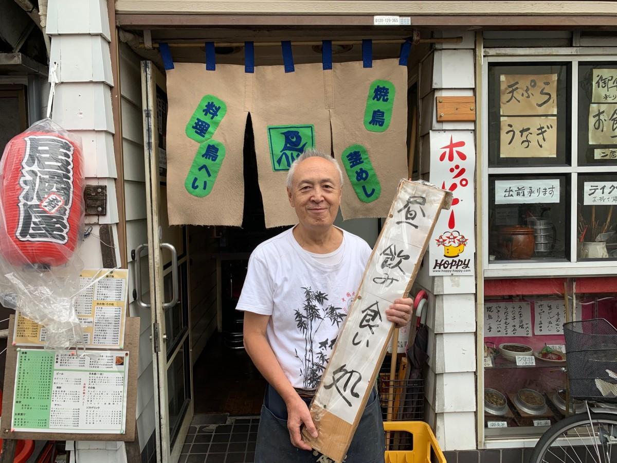 昼営業の看板を持つ「鳥へい」店主・長谷川一平さん