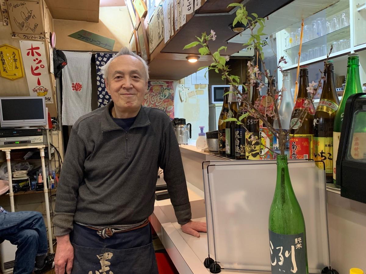 店主の長谷川一平さんと一升瓶にさした桜の枝
