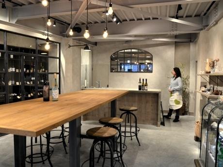 コンクリートと鉄骨のスモーキーな色と質感を生かした内装の店内に天然木の大テーブルを配置