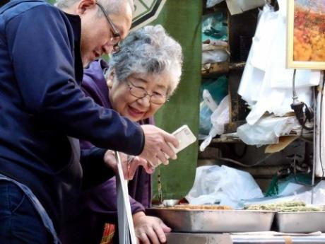 仲見世商店街を取材する細井さん(左)