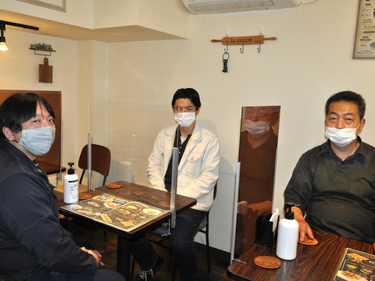テーブル・対面タイプのシールドと、柴田広告社の柴田さん、ヤギ・リカーズの八木さん、GOHANの虎石さん(写真左から)。
