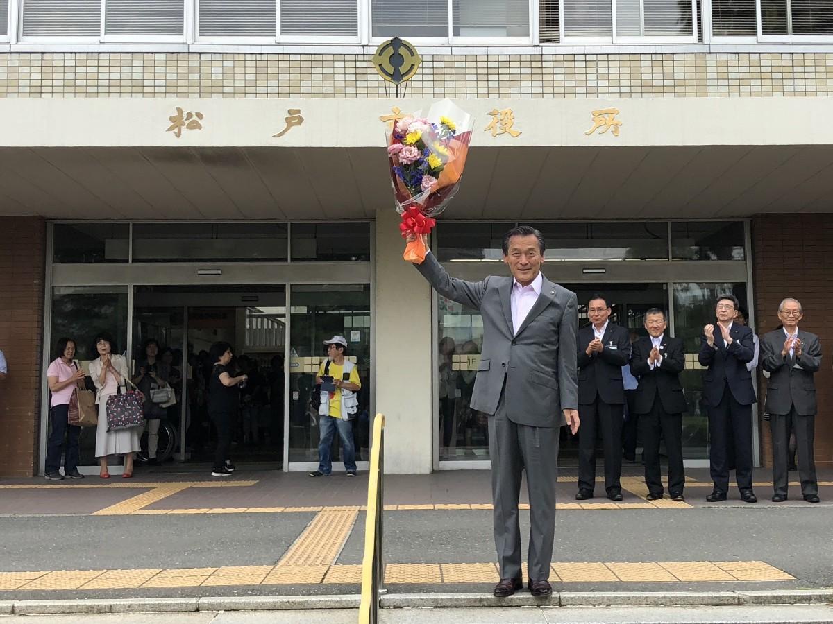 庁舎正面玄関前に立つ本郷谷健次市長