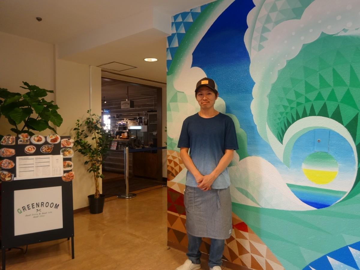 店舗入口の壁画と店長の平山伸昌さん
