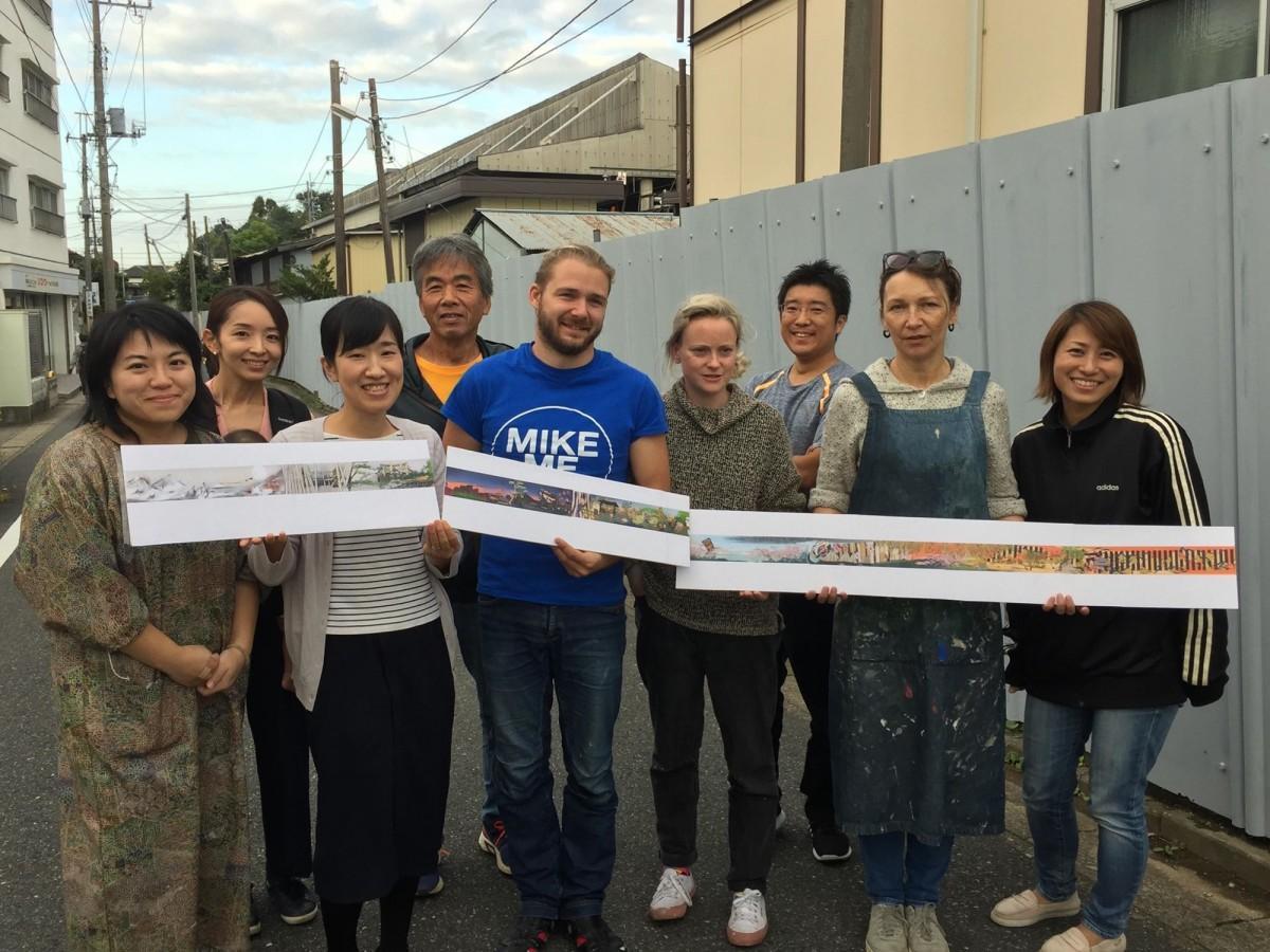 背後の壁で巨大壁画を制作する英国人アーティストのクレア・ウォーレスさん(右から4番目)