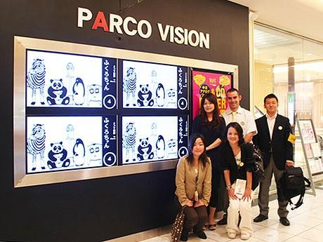 上りエスカレーター脇の「PARCO VISION」。同社スタッフ4人と、松本パルコの重藤さん。