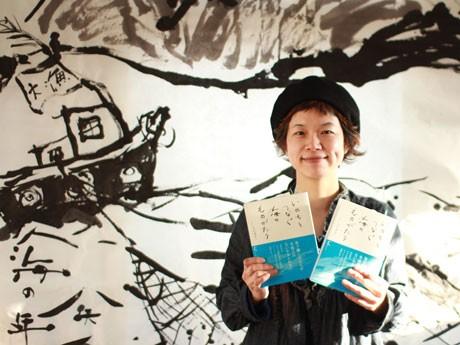 初日に行ったライブペインティングの作品と著書を手にする矢田さん©ウチダゴウ
