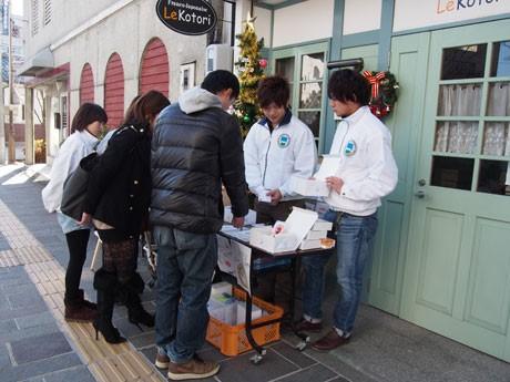 「ル・コトリ」前で企画の説明をする学生たち