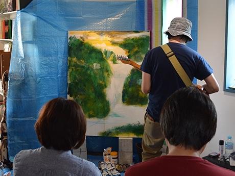 筆とギターを交互に持ち、絵を描いていく植田さん