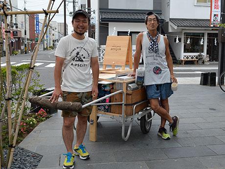 「amijok」前を出発する小島さん(写真左)とカザマさん