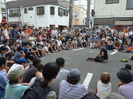 軽快なトークに引き付けられ、観客の輪が広がる