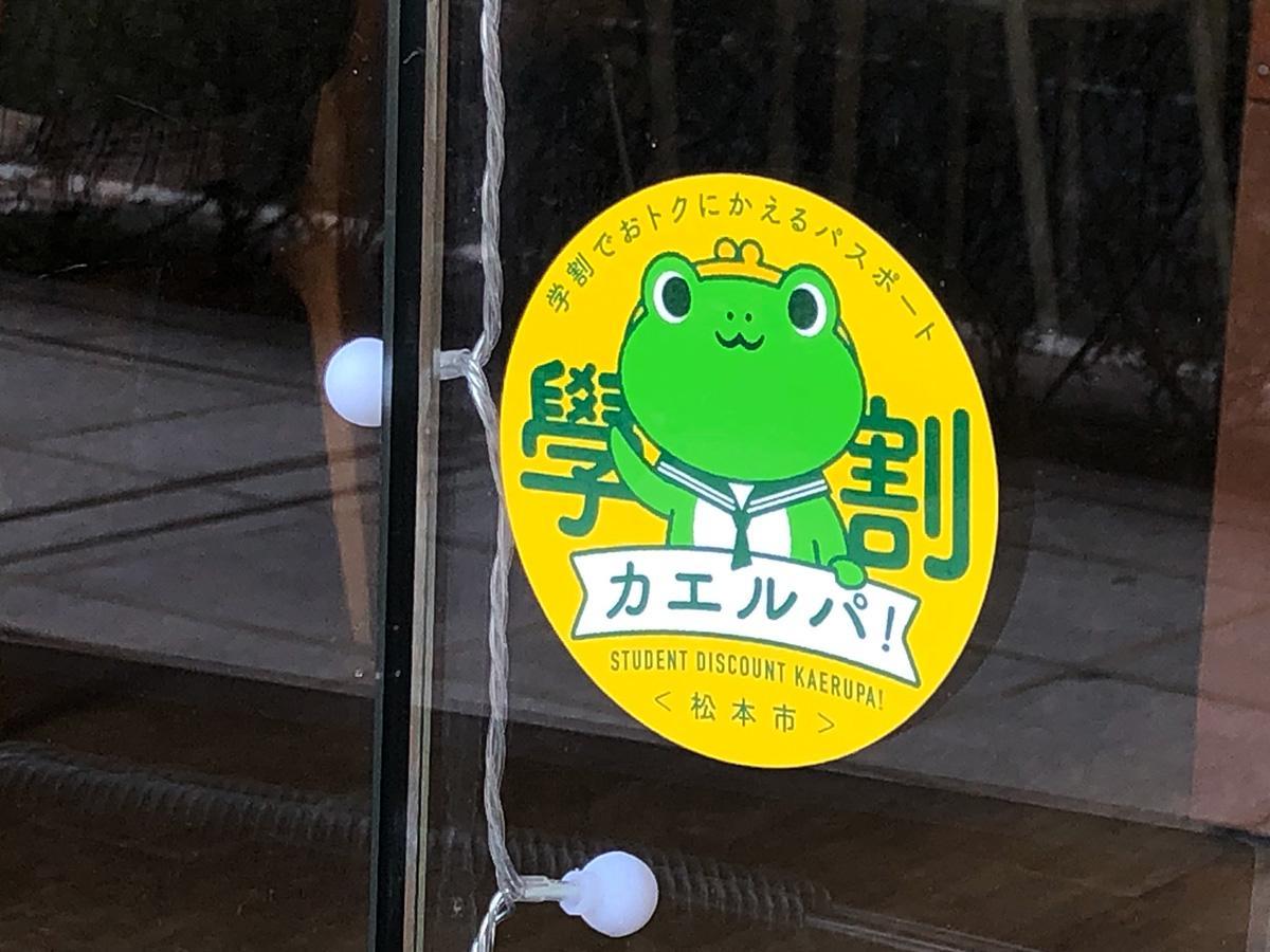 頭ががま口になったカエルが描かれた黄色いステッカーが目印