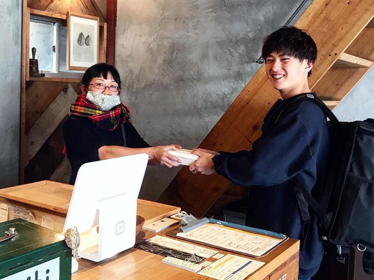 「栞日」でアルバイトをしながら、「モトデリ」を運営する浅川さん(写真右)