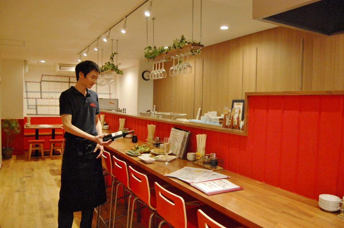 神戸餃子オレギョ松山湊町店の本荘店長と店内の様子。