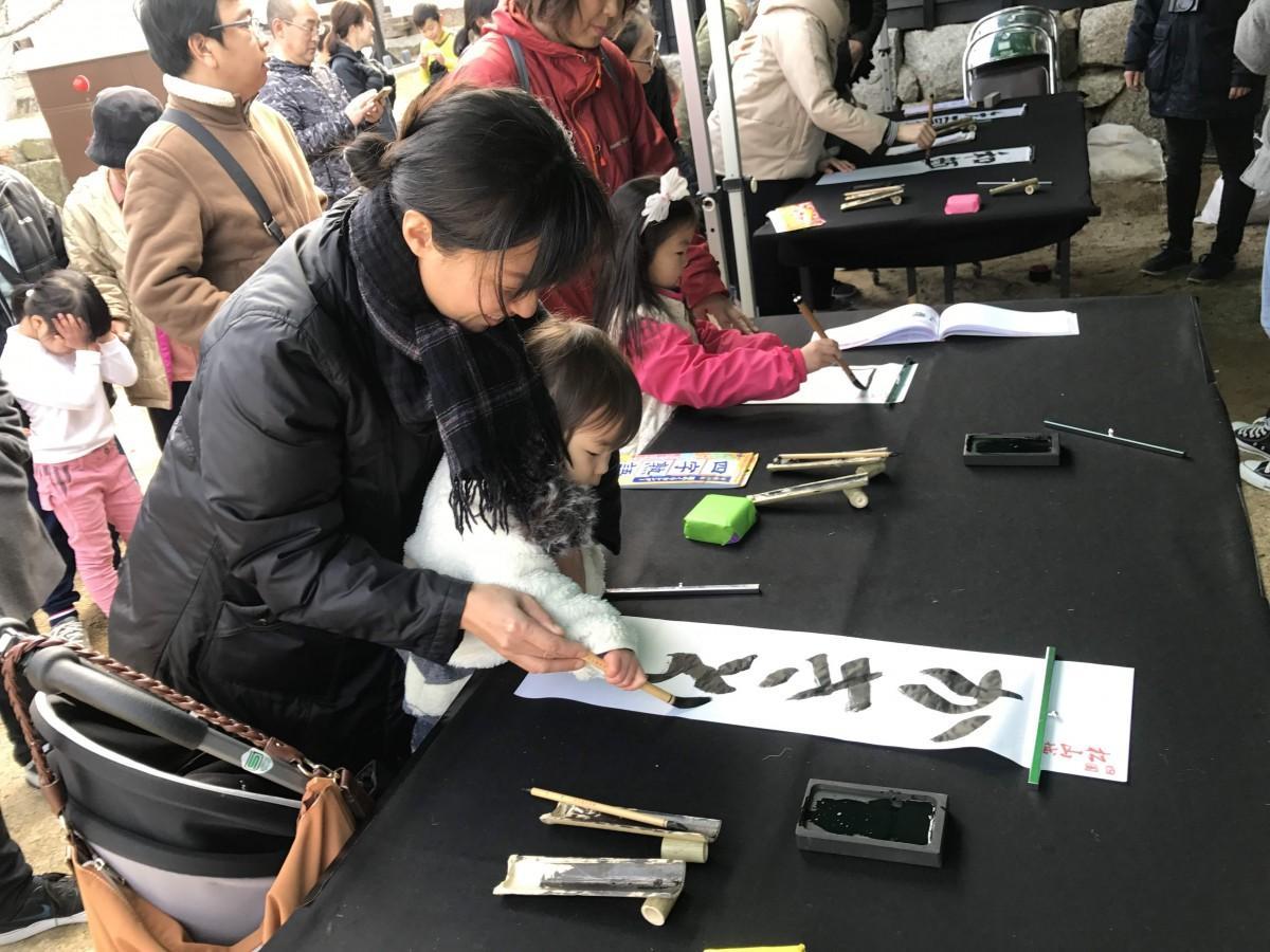 松山城本丸広場で書き初めに挑戦する参加者