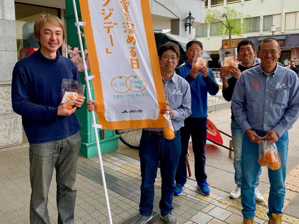 道後温泉商店街入り口でかんきつを配布する西宇和青壮年同志会のメンバー