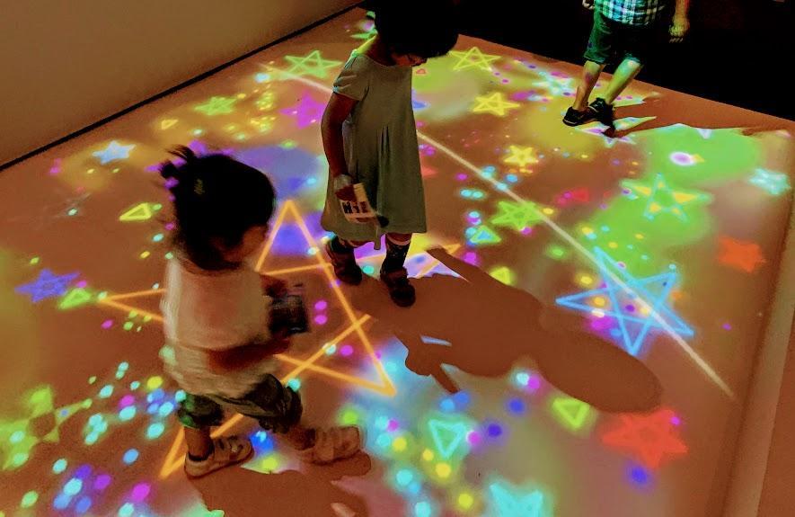 愛媛県美術館「魔法の美術館 光と遊ぼう!マジカル・ワンダーランド」で、坪倉輝明「七色小道」を楽しむ子どもたち