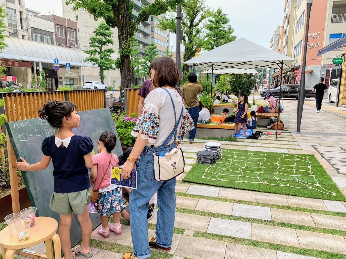 花園町通りに設置された、お絵かき黒板、巨大オセロ、レゴプールなどで遊ぶ子どもたち