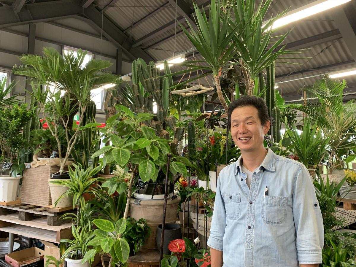 MASAKI本店の「観葉ジャングル」を背景に宮本剛店長。中央奥には目玉商品の「サボテンブランチ」も