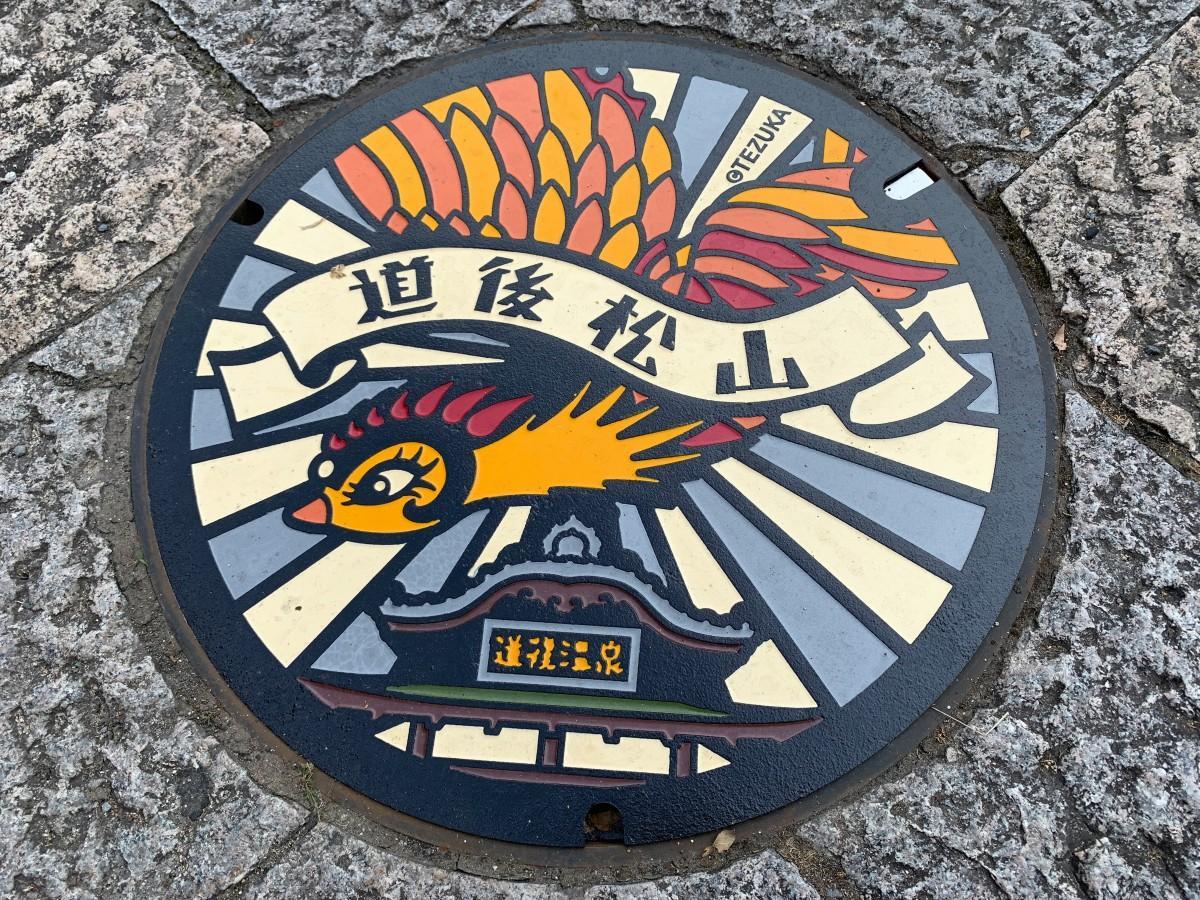 改修工事中の道後温泉本館前に設置された「火の鳥」デザインのマンホールぶた (C)TEZUKA PRODUCTIONS