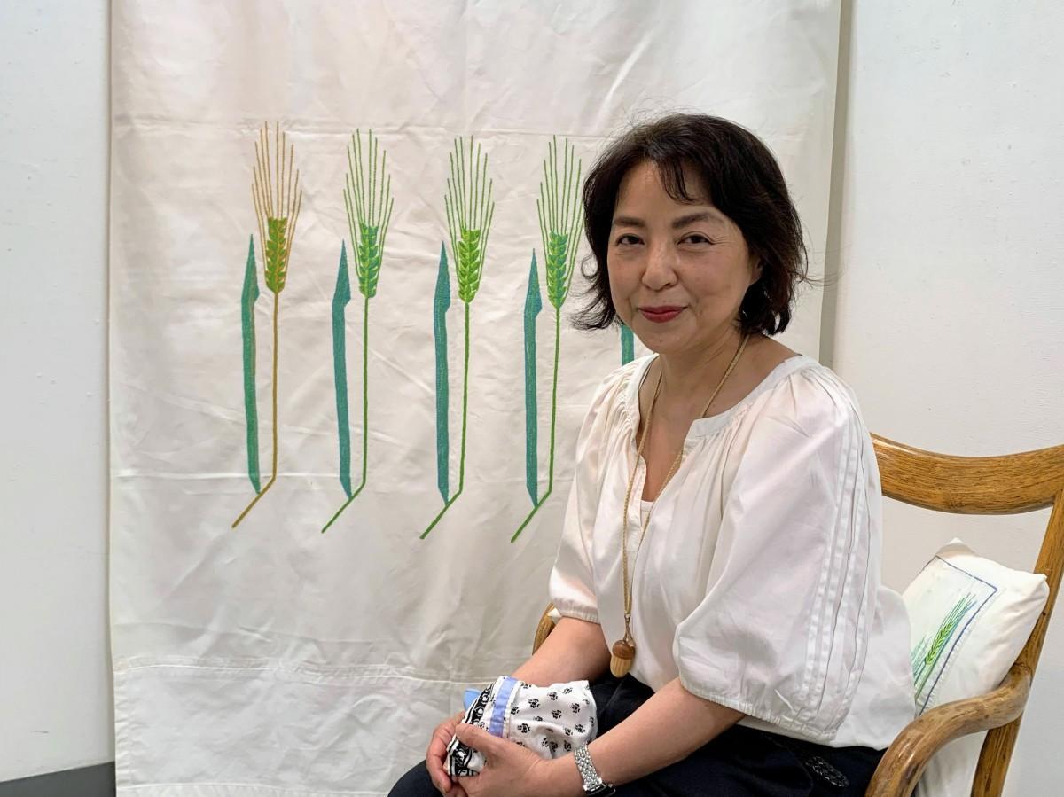 料理家で刺しゅう作家の池内久江さん、大学生のときに母と取り組んだ初めての作品の前で